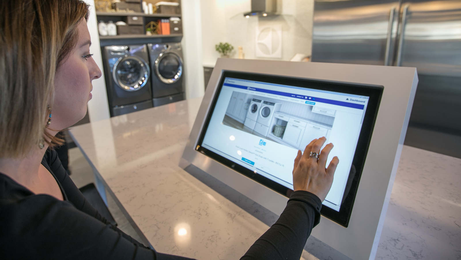 Woman using interactive display system to shop for appliances