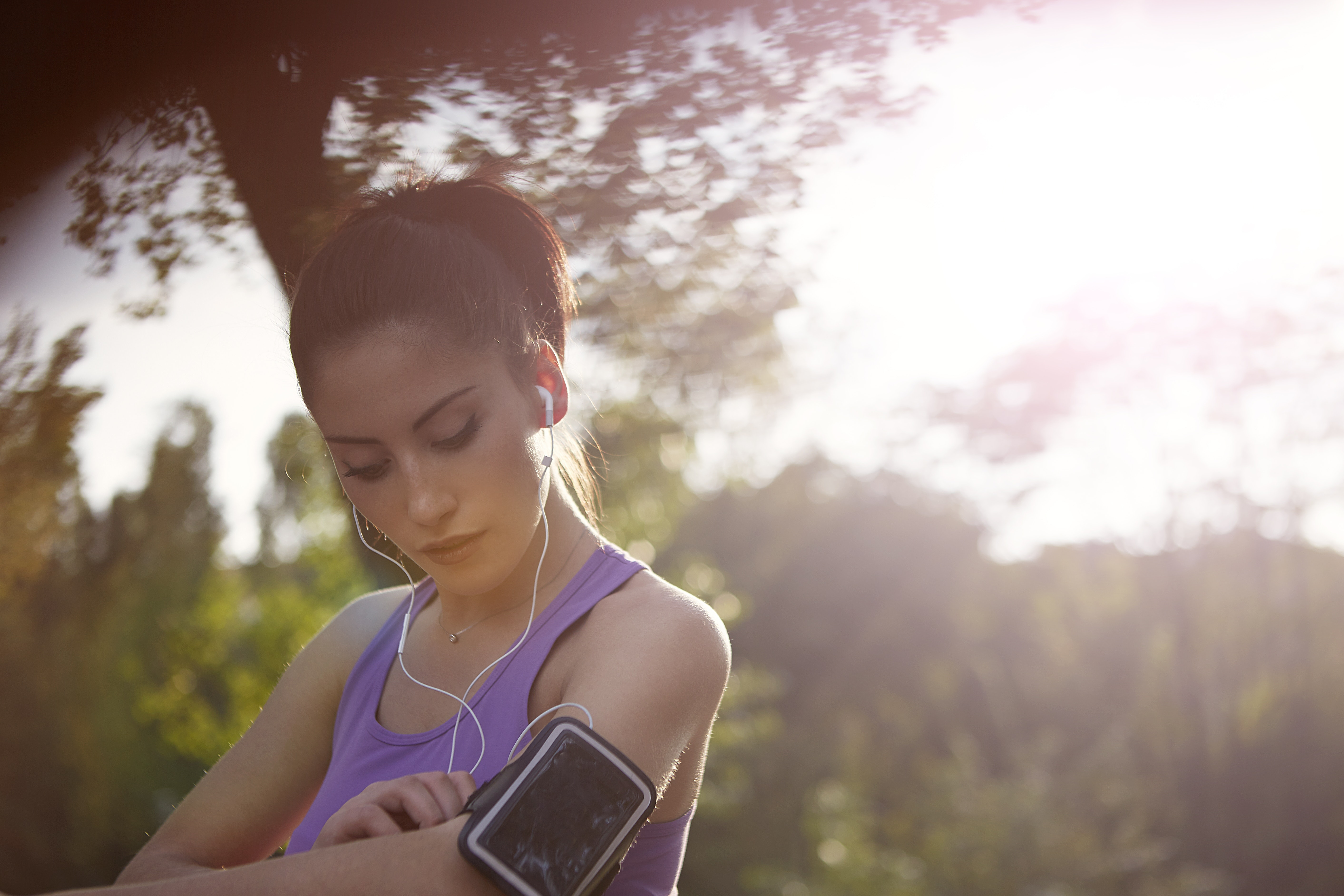young-sportswoman-listening-to-music-in-park-3776837